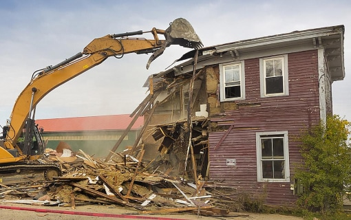 Crane demolishing condemned home