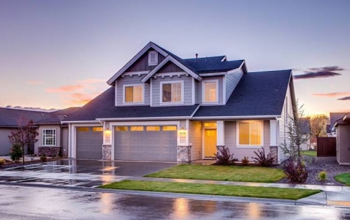 Newly built home lit up with colorful sunset behind
